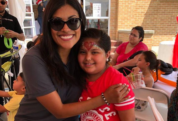 Doctor Pitarra taking a picture with a young patient at community event