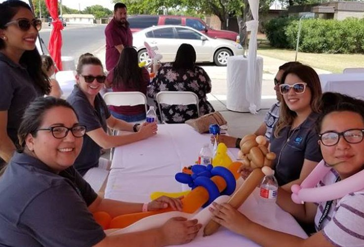 Dental team members sitting at table together during community event