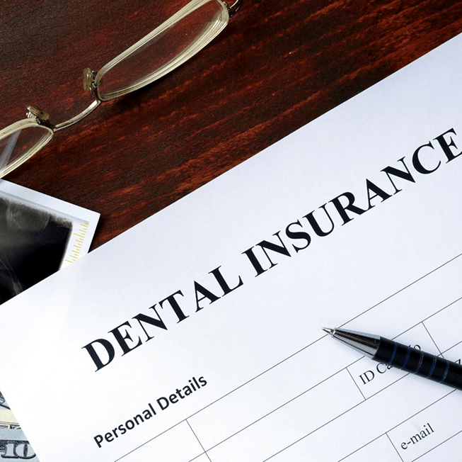 Dental Insurance form on a desk with X-rays and pen