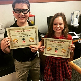 Two children holding cavity free club certificates