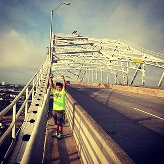Happy child in green shirt on a bridge with arms in air