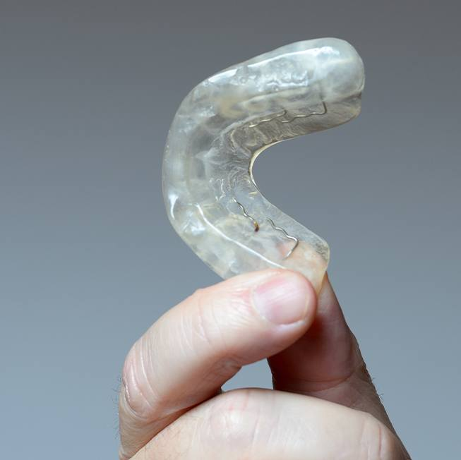 Hand holding a clear aligner for T M J disorder treatment